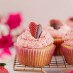 Vegan Strawberry Buttercream Cupcakes by Pasta-based. The cutest strawberry cut into a heart shape and dipped halfway in chocolate. Lined up on a cooling rack with other strawberry buttercream cupcakes and a dozen pink roses in the background. Perfect for Valentine's Day or any special occasion.