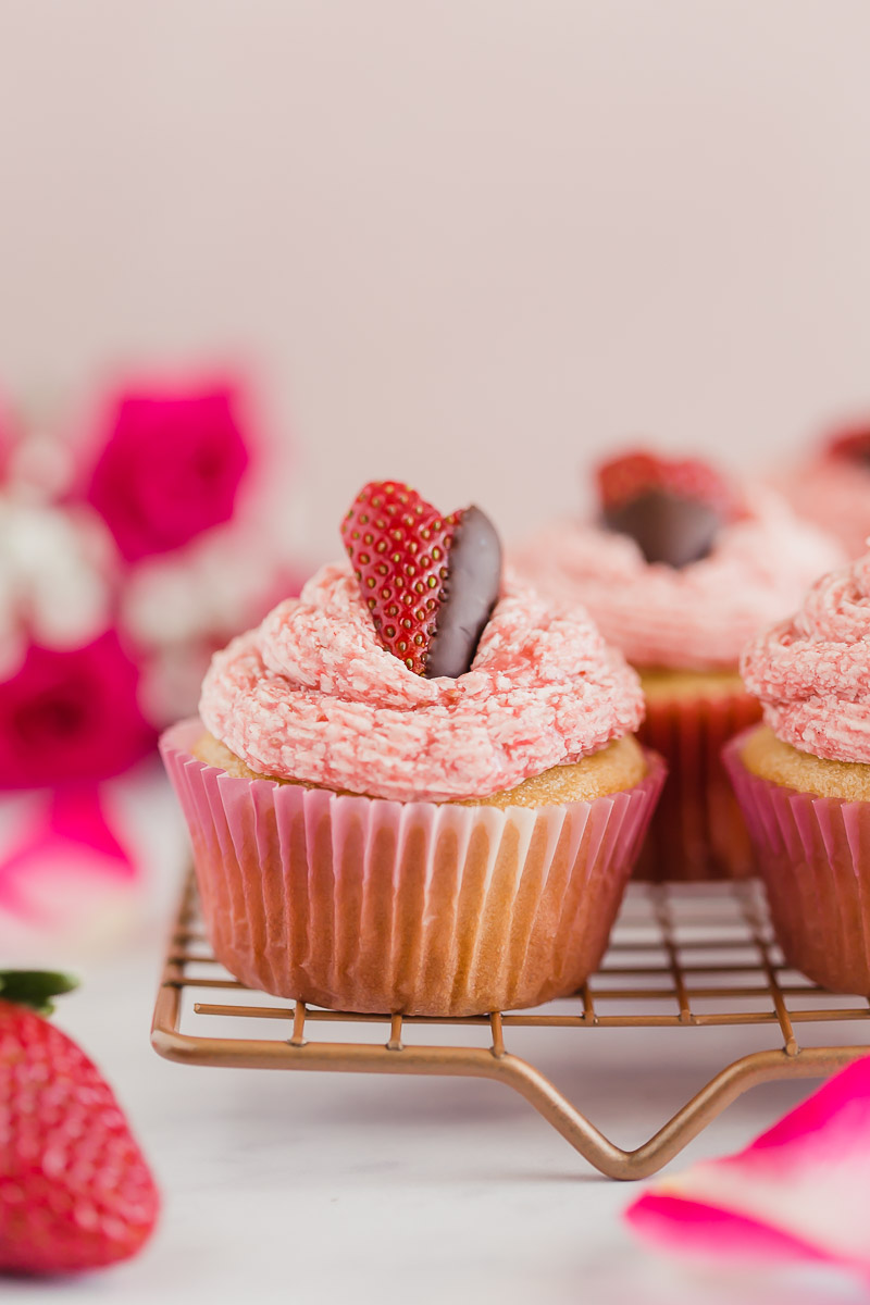 Vegan Strawberry Buttercream Cupcakes by Pasta-based. The cutest strawberry cut into a heart shape and dipped halfway in chocolate. Lined up on a cooling rack with other strawberry buttercream cupcakes and a dozen pink roses in the background. Perfect for Valentines Day or any special occasion.