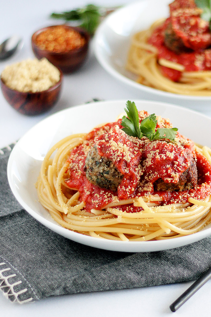 Vegan Meatballs Recipe by Pasta-based. Crispy and browned vegan lentil meatballs on a bowl of spaghetti. Marinara sauce and vegan parmesan cheese on top.