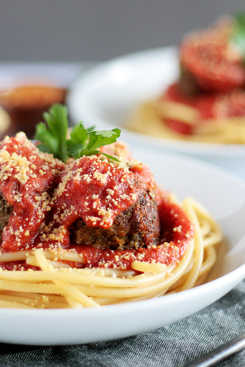 Vegan Meatballs Recipe by Pasta-based.  Perfectly browned lentil and mushroom meatballs on top of a swirl of spaghetti with red tomato sauce poured on top.