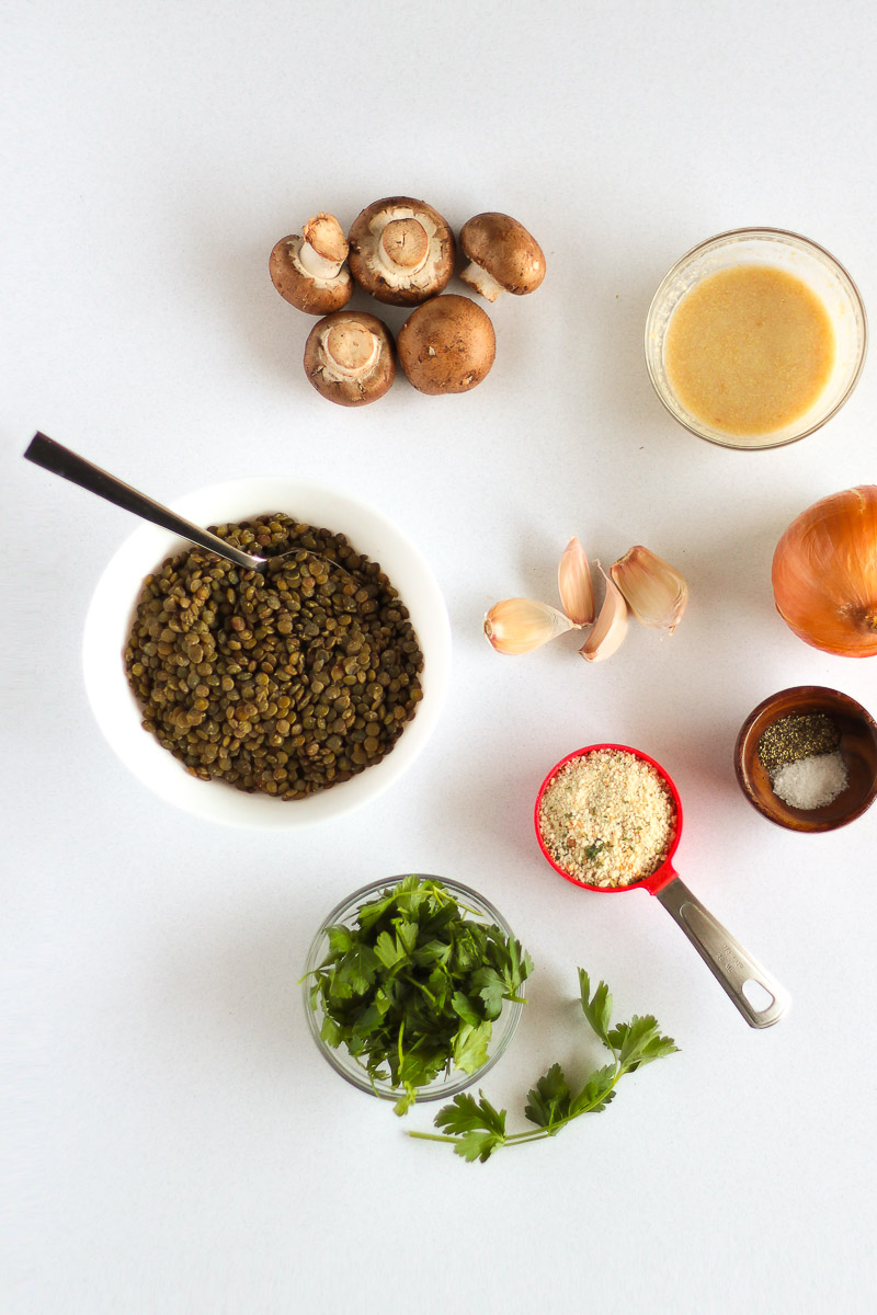 Vegan Meatballs Recipe by Pasta-based. Lentils, Italian-seasoned breadcrumbs, cremini baby bella mushrooms, fresh onion, fresh garlic cloves, flax egg, fresh parsley, and salt and pepper in a small wooden bowl.