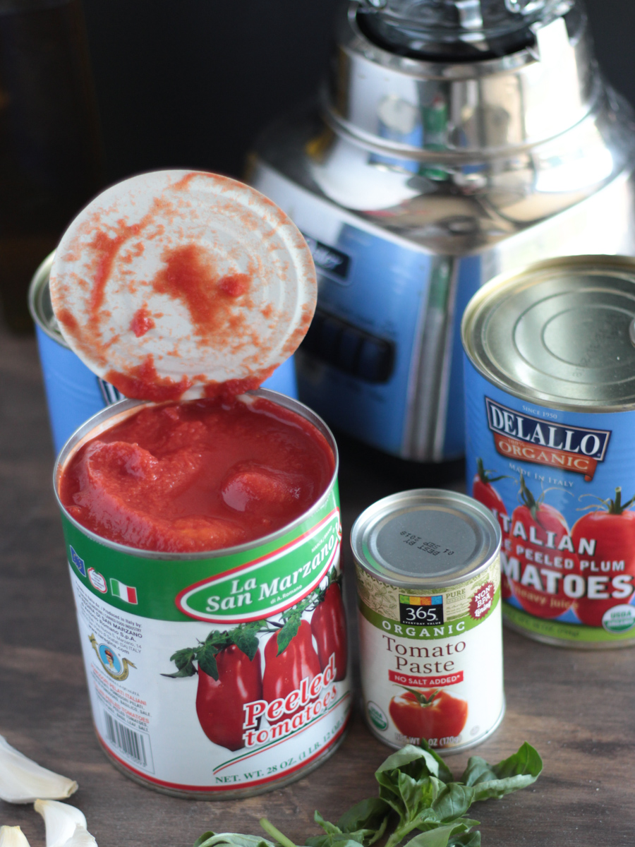 Tomato sauce ingredients picture.  San Marzano tomatoes in a can, tomato paste, garlic and a blender in the background.