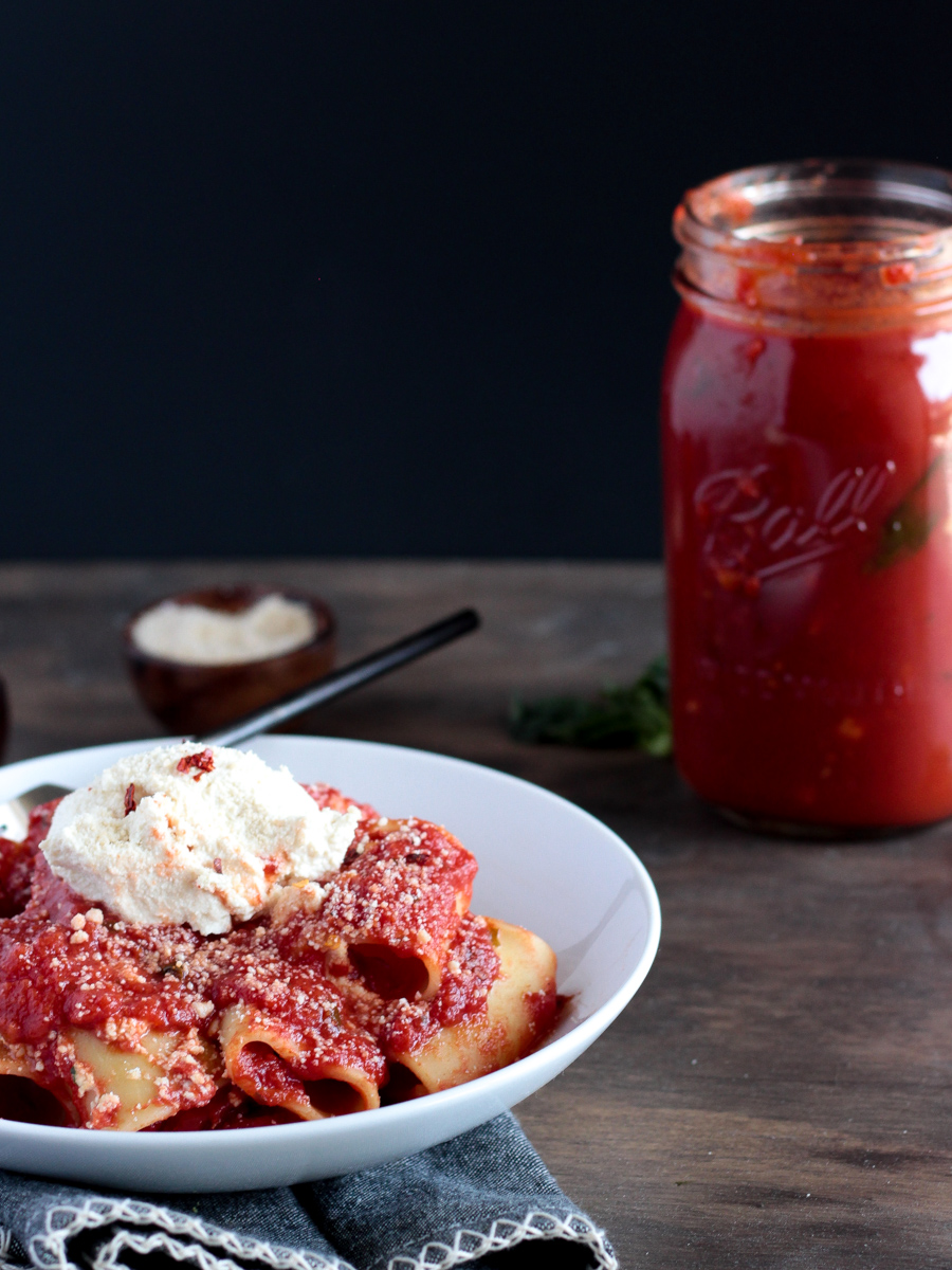 white plate with pasta and tomato sauce with ricotta on top.  Jar of sauce in background
