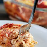Spaghetti Squash Lasagna (Vegan and Gluten-free) by Pasta-based. Someone is taking a forkful of spaghetti squash lasagna with creamy vegan ricotta cheese melting out.