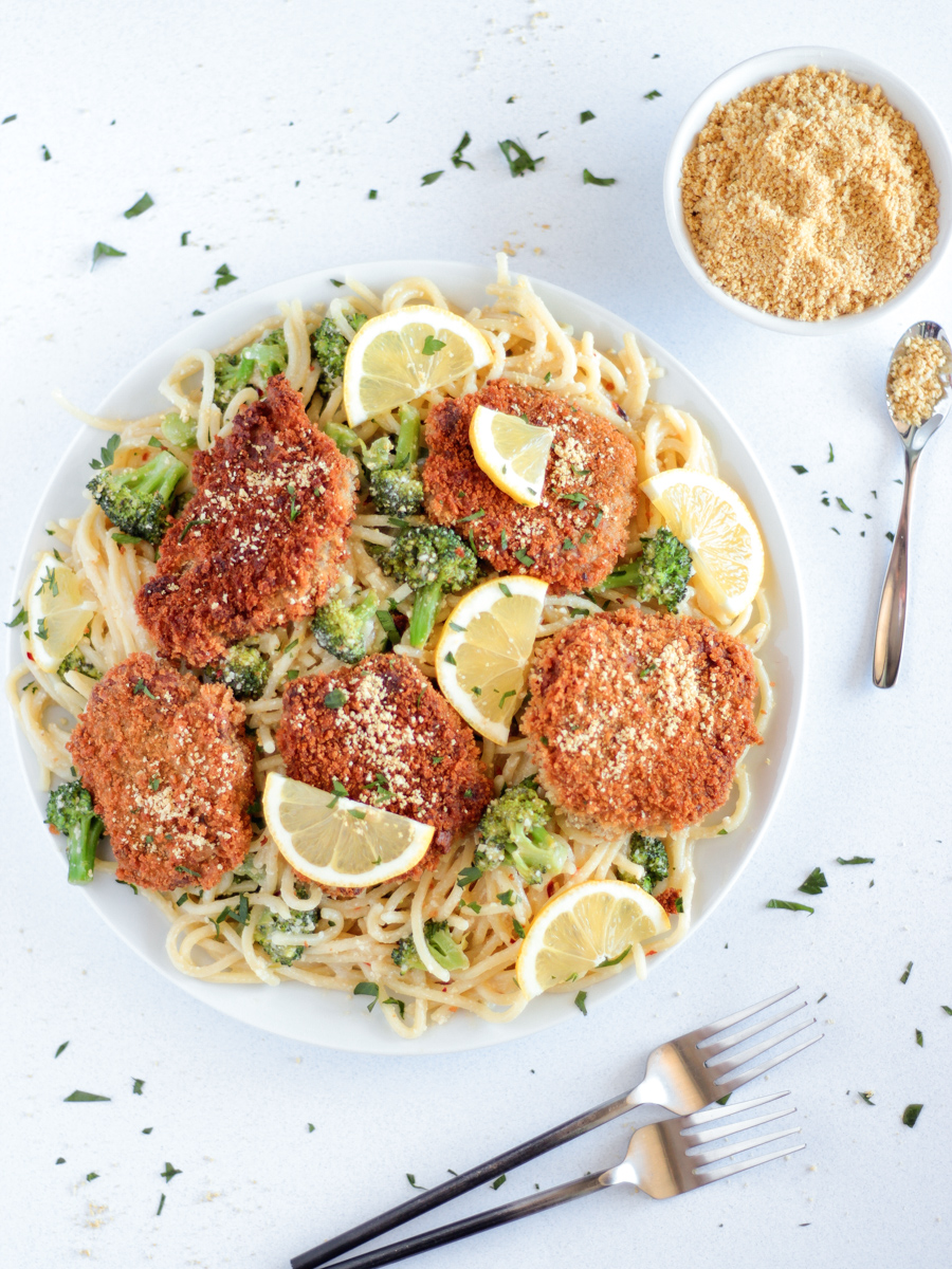 The Best chicken-style seitan cutlets on a white plate on top of spaghetti with broccoli and lemon slices.