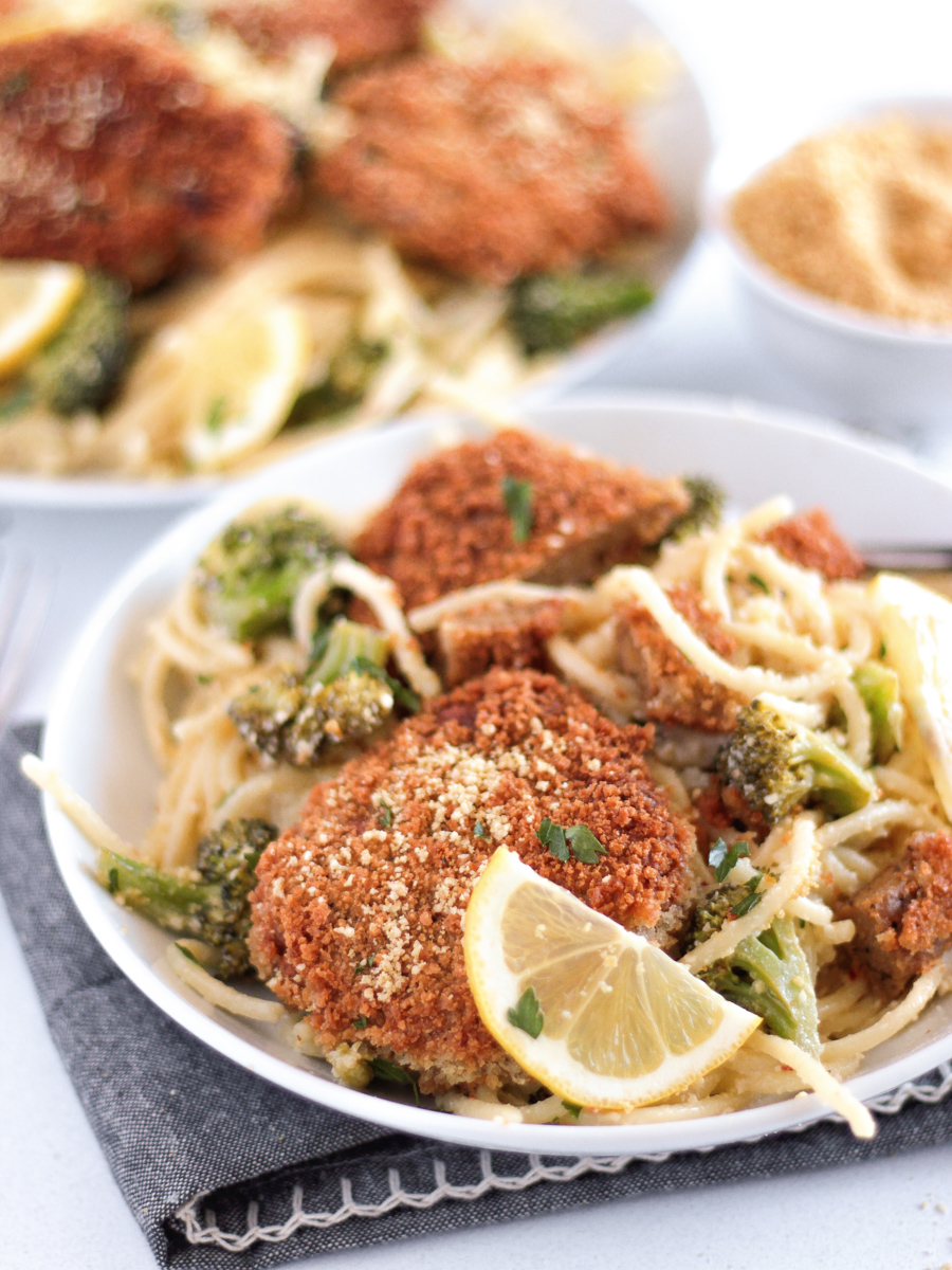 Fried vegan chicken cutlets on a white plate on top of spaghetti with broccoli and lemon slices.