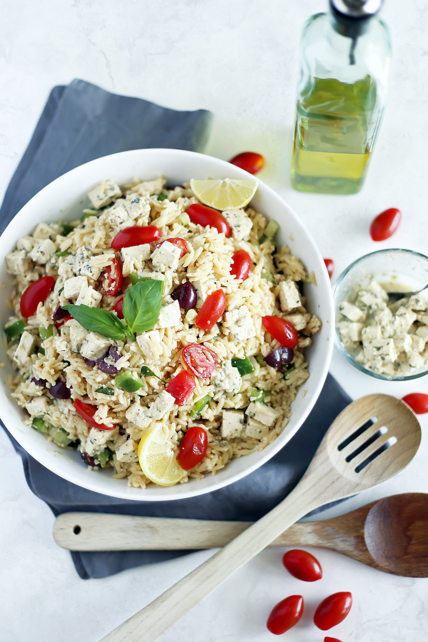 Vegan Orzo Pasta Salad by Pasta-based. A large white bowl piled high with orzo salad. Sprinkled with Homemade Tofu Feta, fresh grape tomatoes, and Dijon Mustard Vinaigrette.