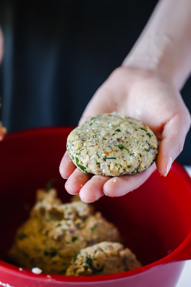 Shaping the patties of vegan tempeh slides, about the size of the palm of your hand.
