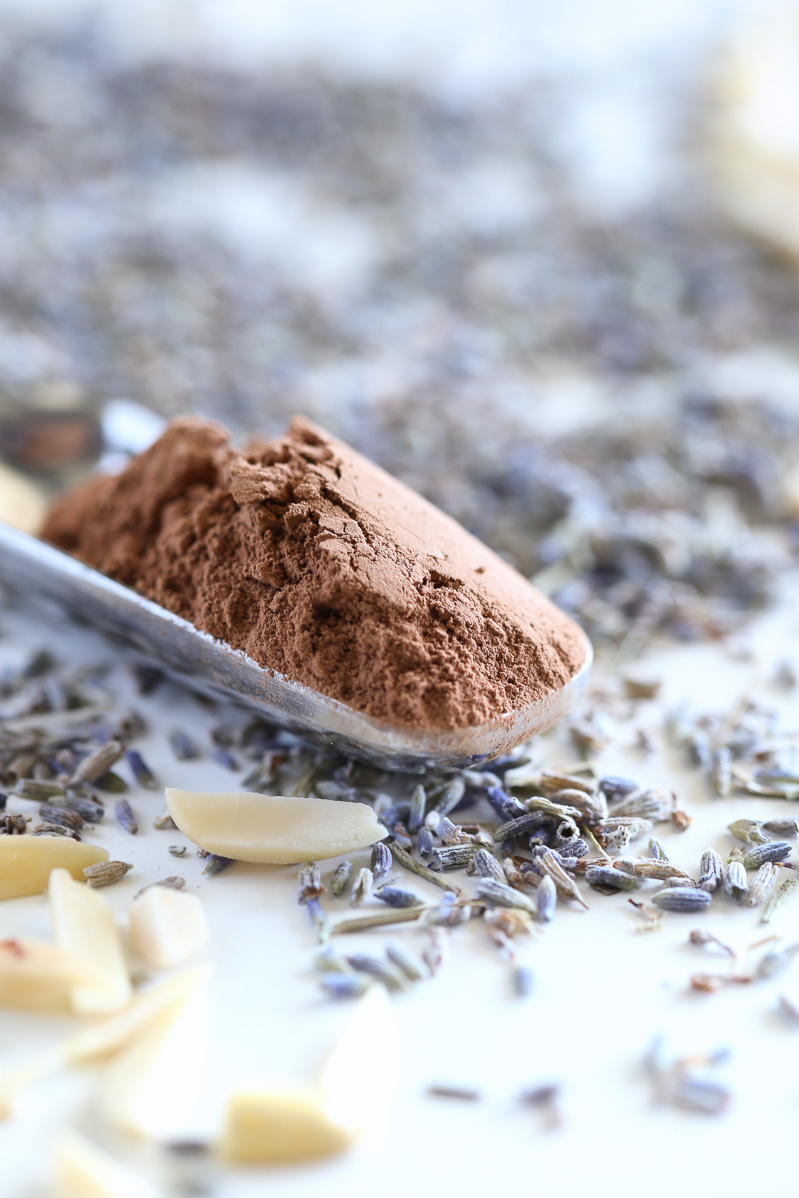 A small scoop of cocoa powder in a silver scoop, on a white table with lavender buds, and blanched almonds randomly placed around it.