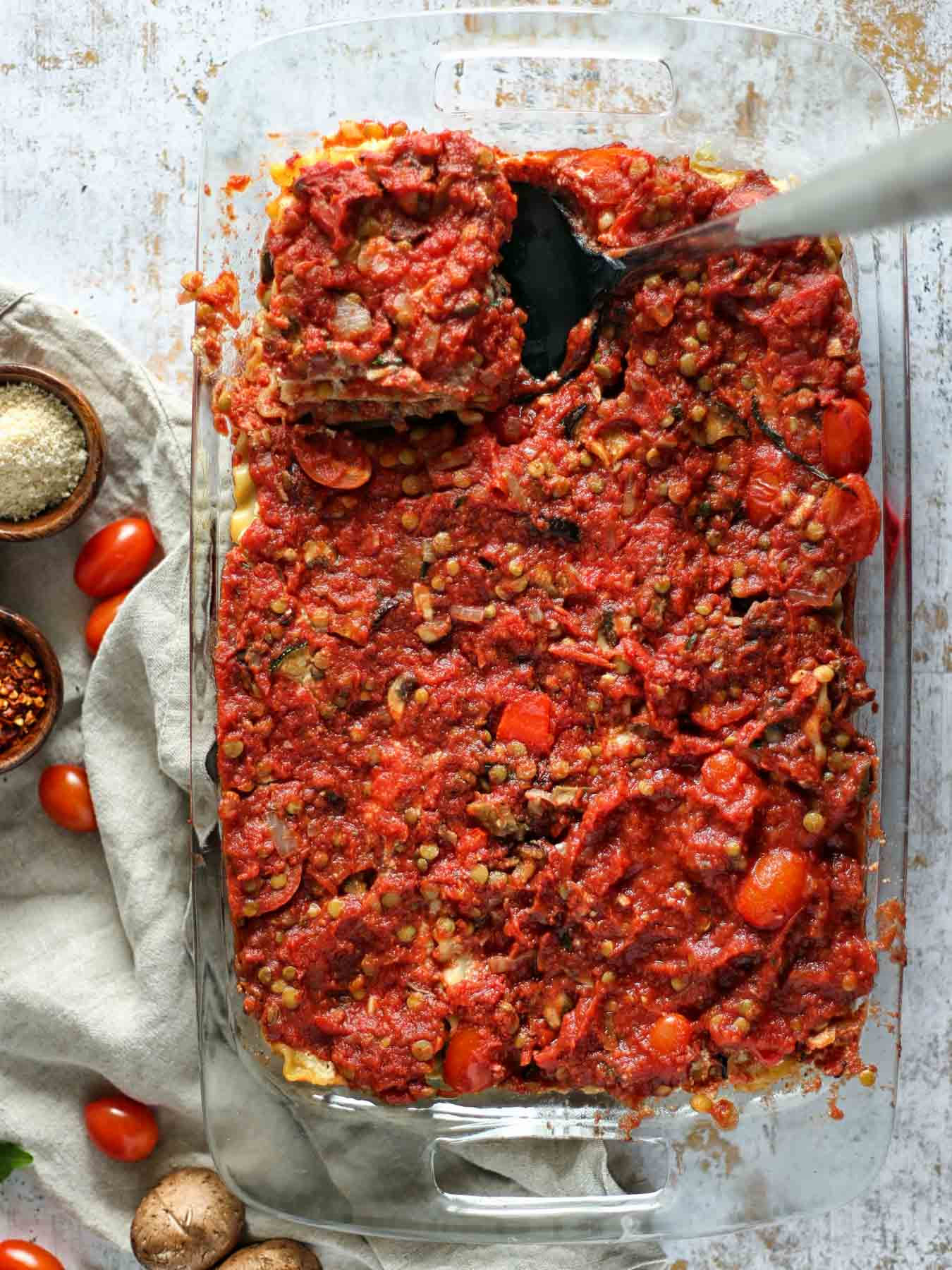 The vegan lasagna consists of four layers: our homemade lentil bolognese sauce, cooked lasagna noodles, homemade almond ricotta cheese and roasted vegetables (eggplant, zucchini, and red pepper)