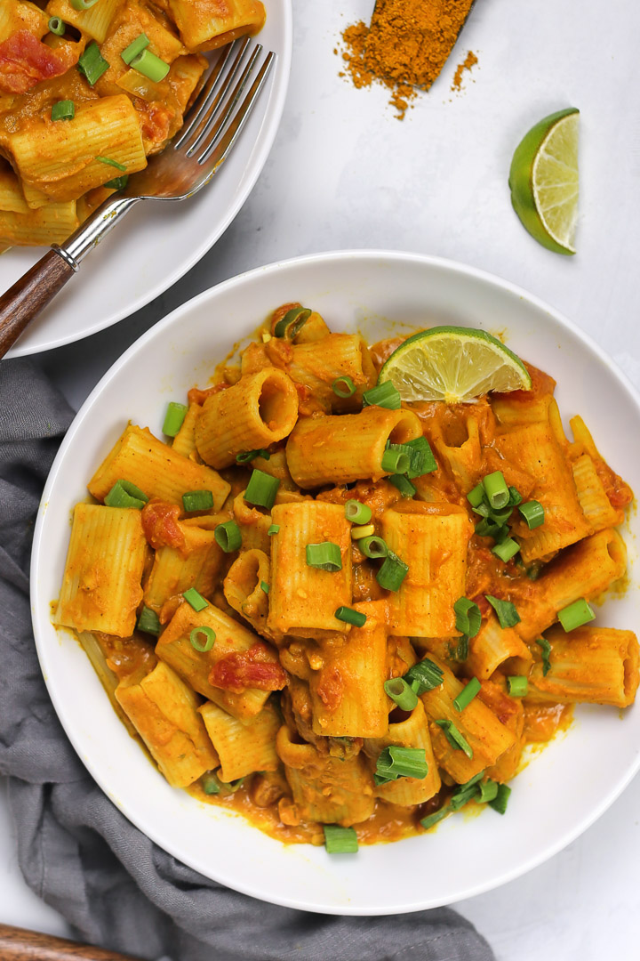 An overhead shot of creamy, Vegan Pumpkin Curry Pasta with chopped green onions on top in a white bowl with slices of lime.