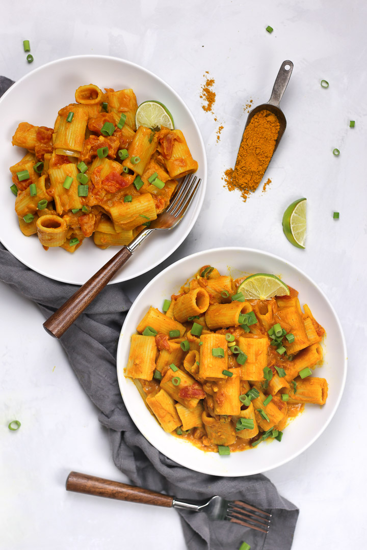 Creamy Vegan Pumpkin Rigatoni Pasta with Pumpkin Puree, Curry Powder, and Coconut Cream, topped with Green Onions and Lime