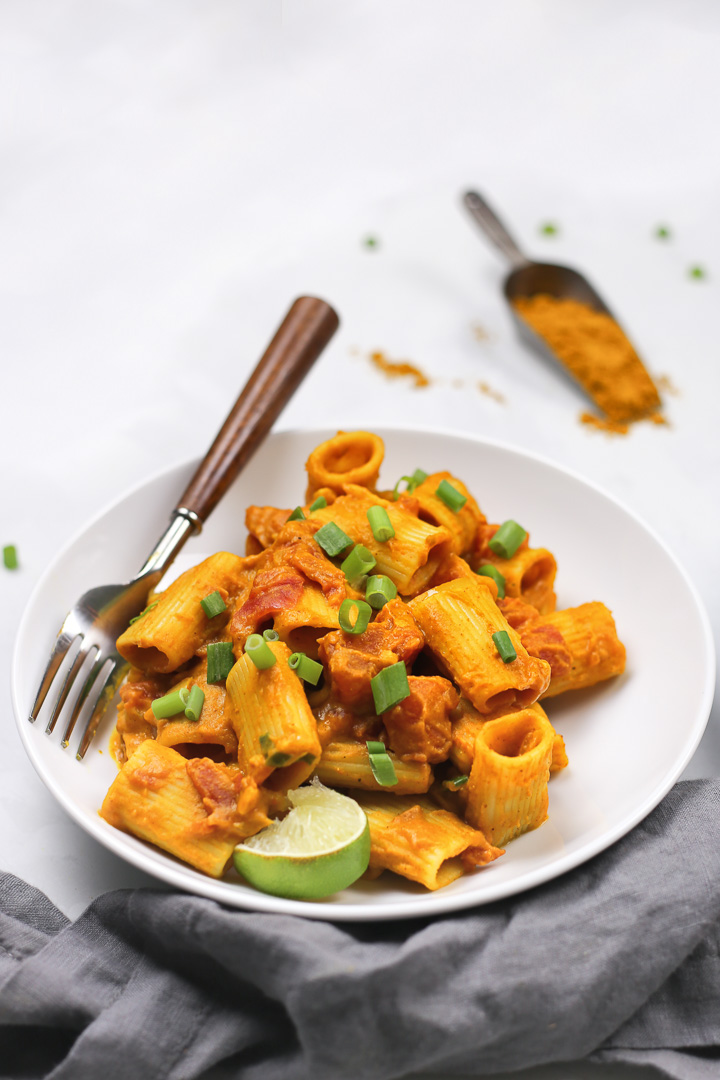 Vegan Pumpkin Curry Pasta in a white bowl and a scoop of curry powder spilling in the background.