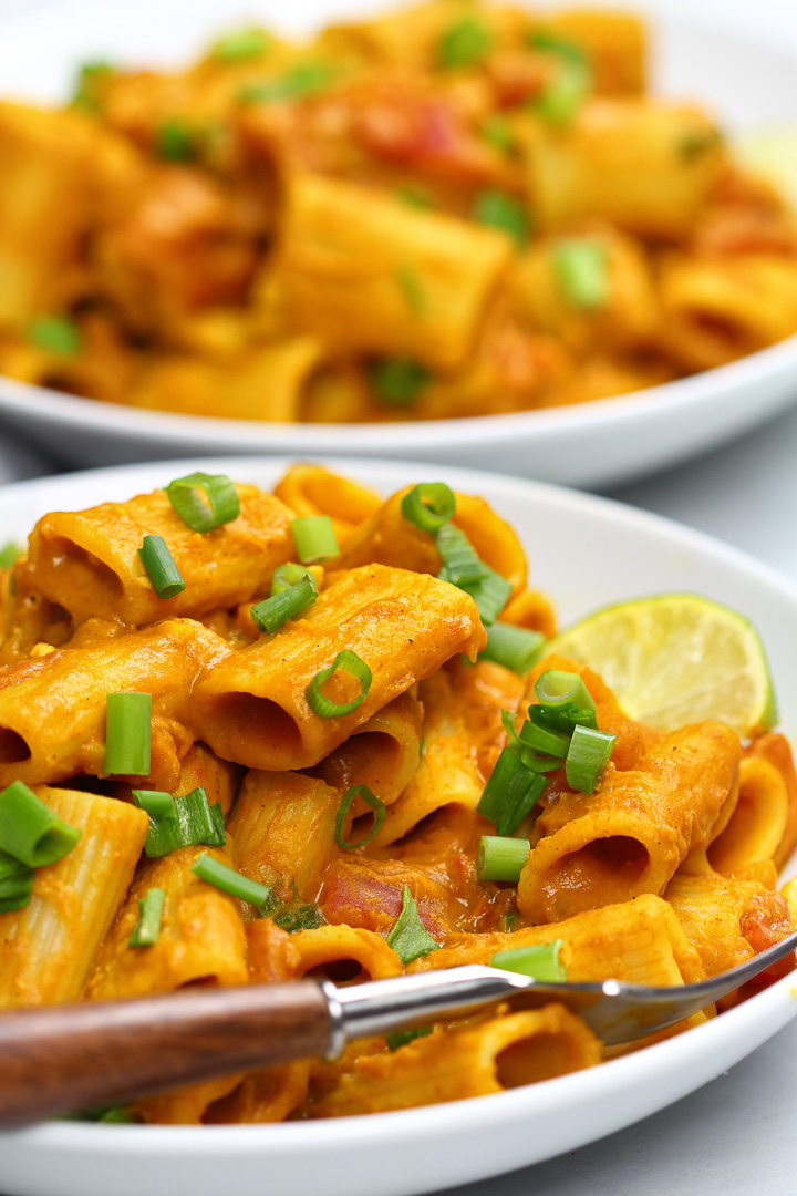 A close-up photo of the creamy texture of the Pumpkin Curry Pasta with bright green chives garnished on top.