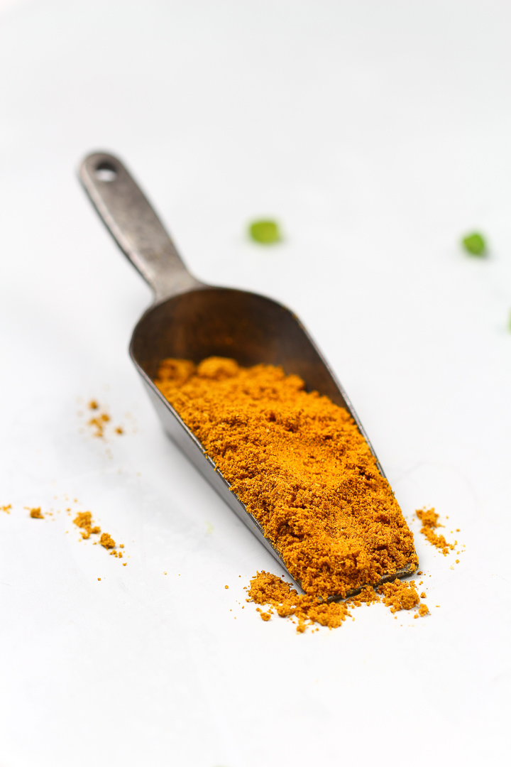A scoop of bright orange curry powder.