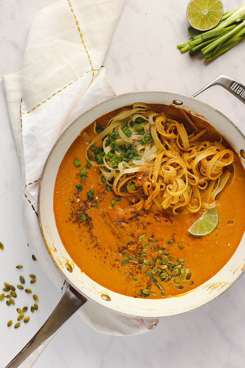 Vegan Pumpkin Curry Pasta by Pasta-based. A large pan with creamy, pumpkin curry pasta sauce with fettuccine, freshly chopped green onions, a sprinkle of nutmeg, roasted pepitas and a lime wedge.