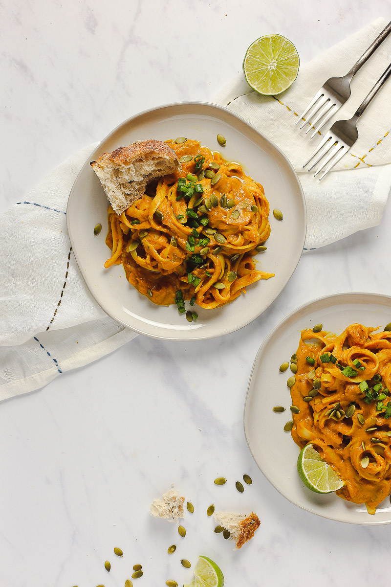 Vegan Pumpkin Curry Pasta by Pasta-based. Two white plates on a marble surface with a white embroidered dish towel underneath one of the plates. Two forks peak out the top-right of the frame beside a bright green lime sliced in half. Fettuccine smothered in a creamy, pumpkin curry pasta sauce is piled in the middle of both plates. Both plates have garnishes like roasted pepitas, freshly chopped green onion, lime wedges, and kalamata-olive garlic bread.
