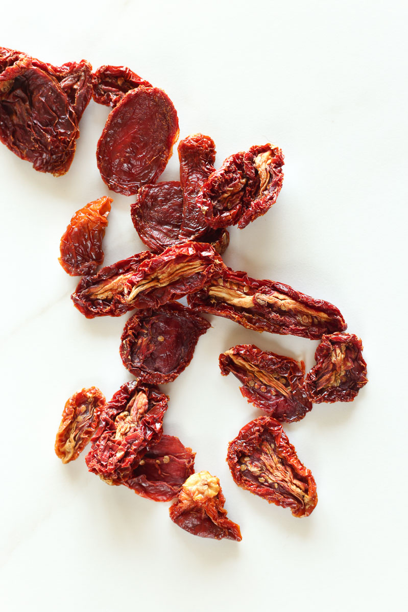 Bright red sun dried tomatoes scattered on a white table