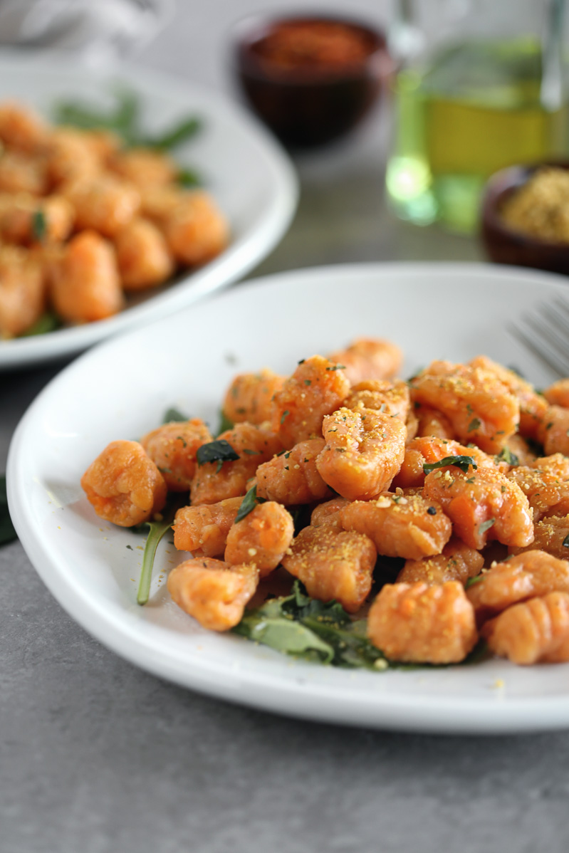 Orange gnocchi on a white plate garnished with greens, and nutritional yeast cashew parmesan.