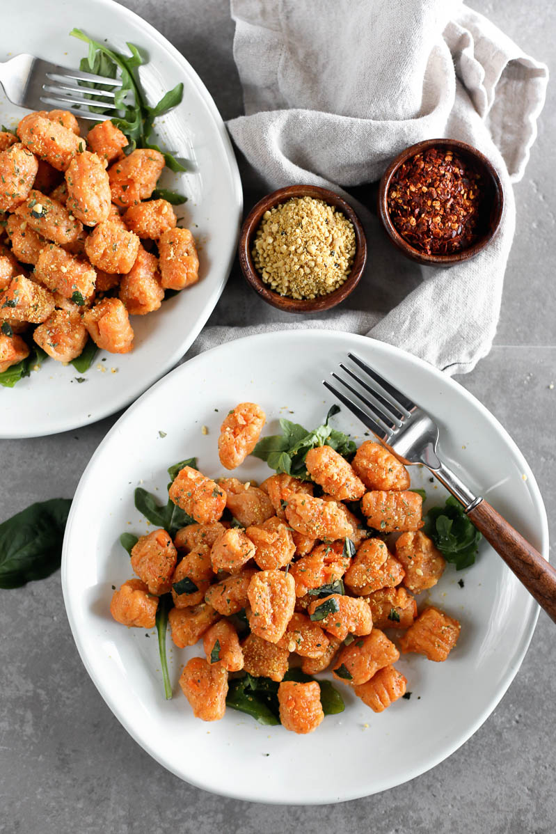 Vegan Sweet Potato Gnocchi by Pasta-based. Overhead photo of two white plates with cooked sweet potato gnocchi. Two small wooden bowls filled with cashew parmesan and red pepper flakes on the side.