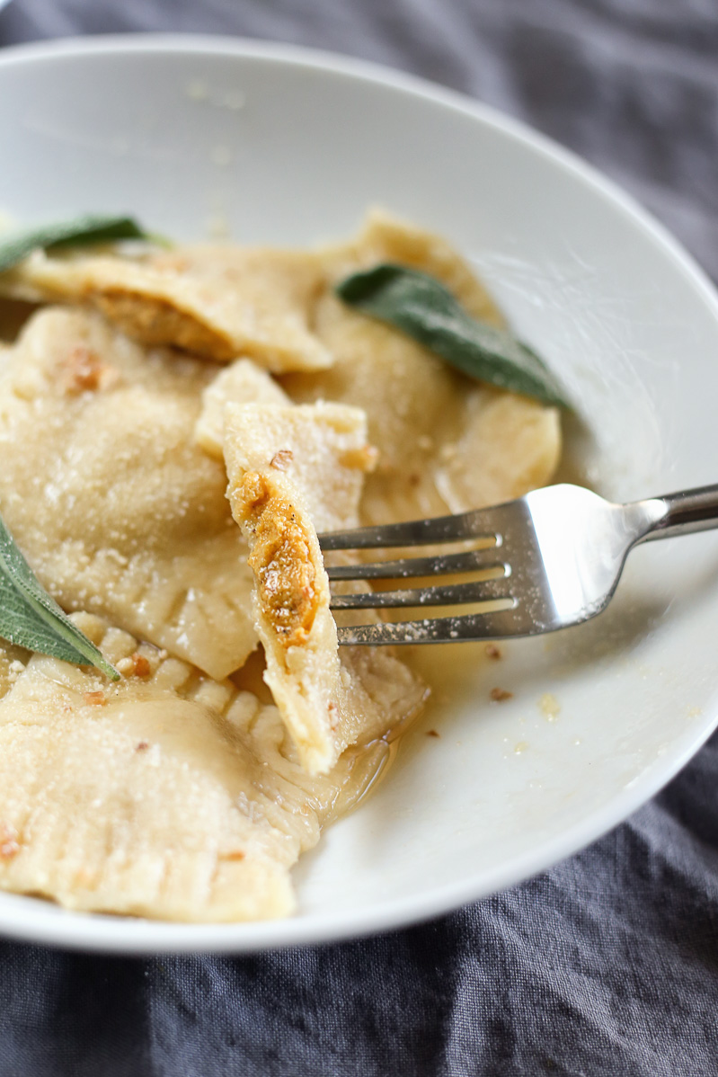 Vegan Butternut Squash Ravioli by Pasta-based. A butternut squash ravioli cut in half and on a fork, resting on top of the other raviolis in a dish, showing the delicious filling stuffed inside.