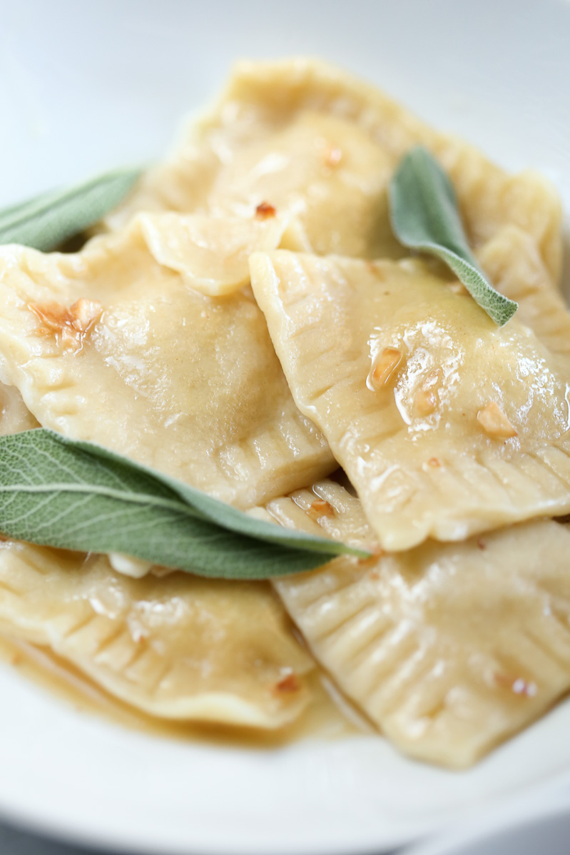 Vegan Butternut Squash Ravioli by Pasta-based. Finished and cooked ravioli nestled together on a white plate covered in a sage, garlic, brown-butter sauce with fresh sage leaves for garnish.