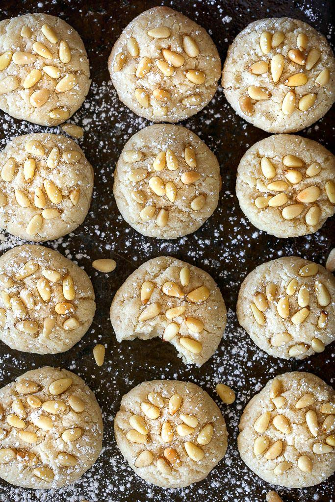 Vegan Italian Pignoli Cookies by Pasta-based. An overhead shot of the baked pignoli cookies on the baking sheet with powdered sugar sprinkled on them.