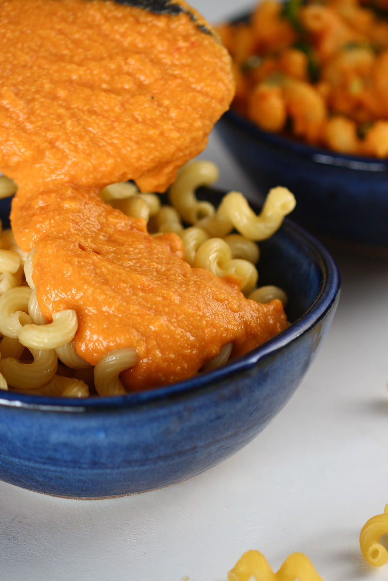 Vegan Mac and Cheese by Pasta-based. Creamy and smooth vegan Cheese Sauce being poured over pasta noodles in a deep blue bowl.