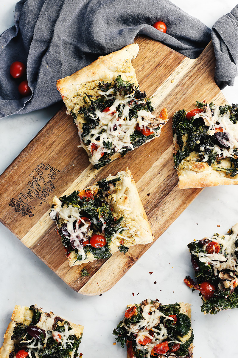 Vegan Crispy Kale Grandma-Style Pizza by Pasta-based. A top-down shot of a few slices of pizza on a table.