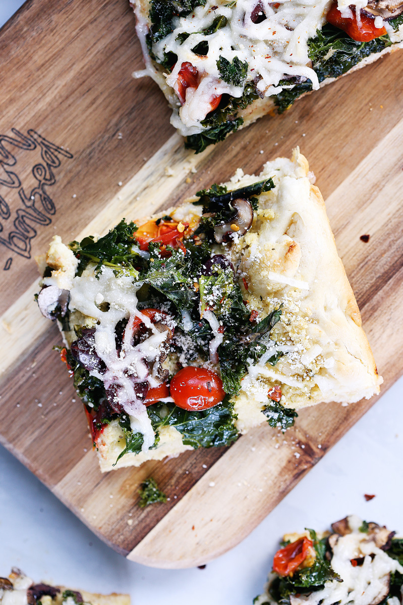 Vegan Crispy Kale Grandma-Style Pizza by Pasta-based. A top-down shot of a square slice of pizza on a cutting board.