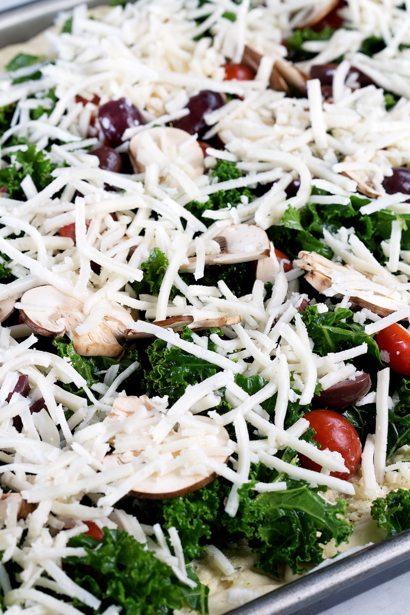 Vegan Crispy Kale Grandma-Style Pizza by Pasta-based. A close-up of the pizza before going into the oven.