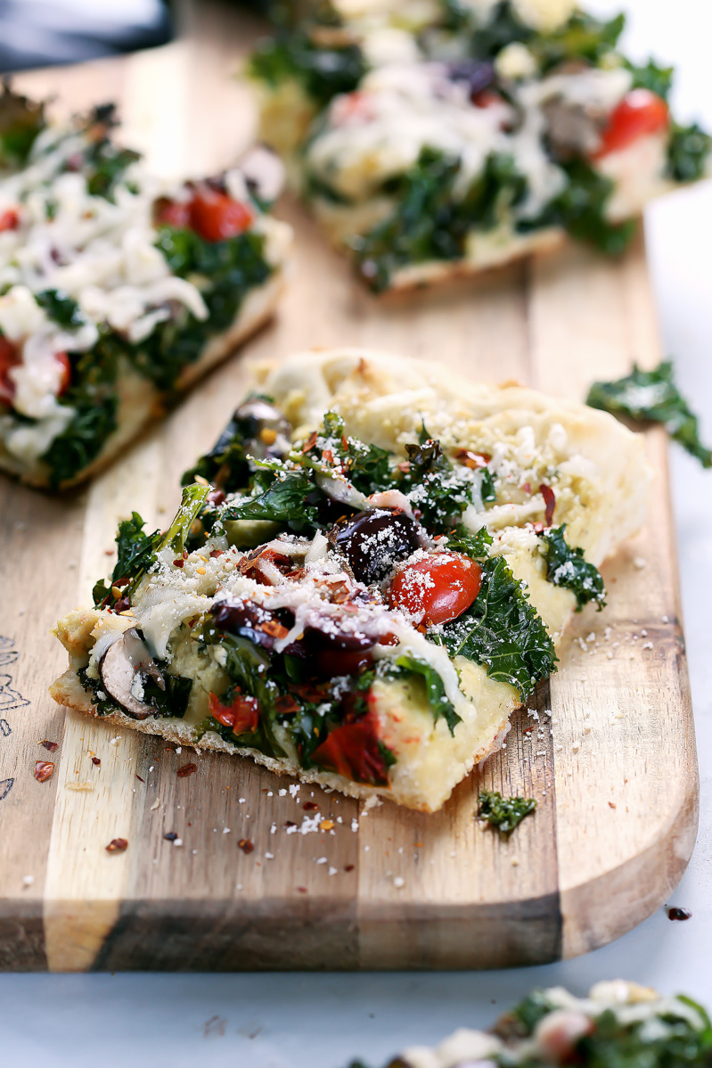 Vegan Crispy Kale Grandma-Style Pizza by Pasta-based. A square slice of pizza on a cutting board.