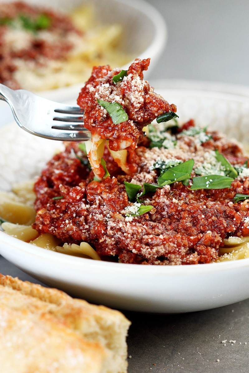 Vegan Cauliflower Walnut Bolognese by Pasta-based. Detailed view of a forkful of cauliflower walnut bolognese sauce/vegan meat sauce with farfalle pasta.