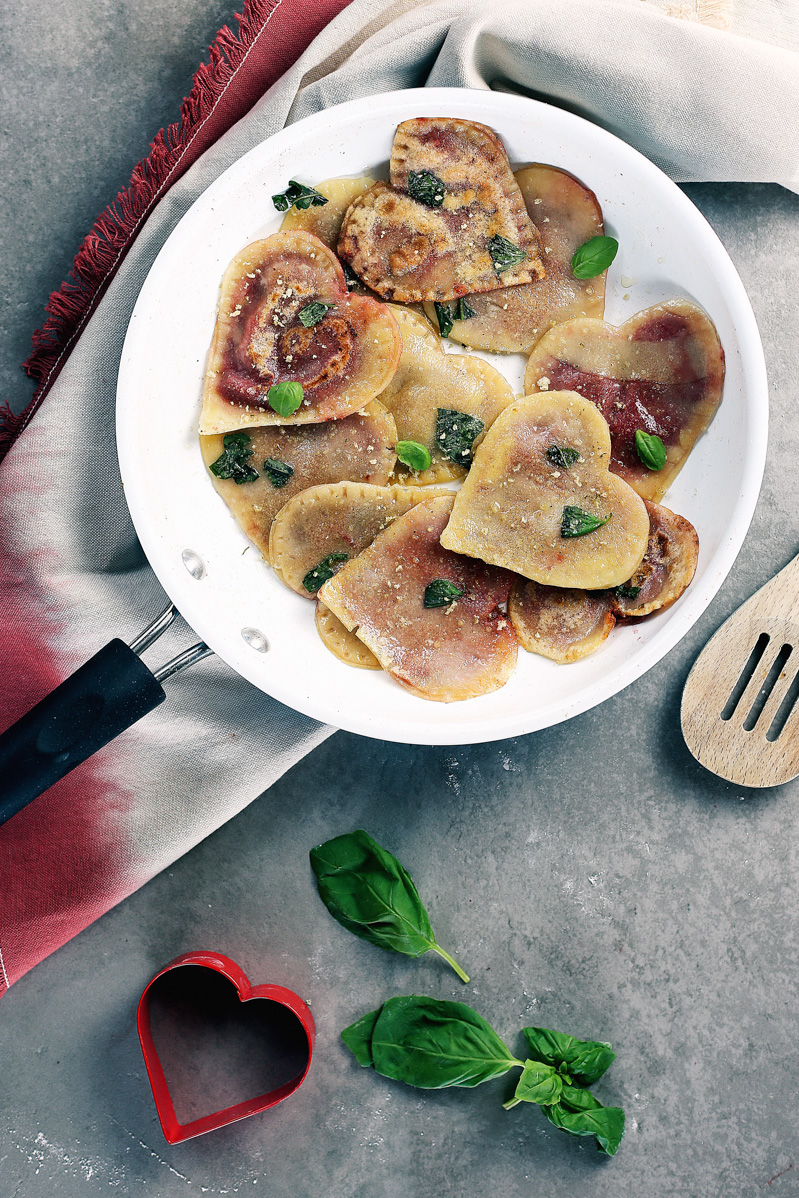Vegan Red Beet Pesto Ravioli by Pasta-based. Lightly crisped vegan heart-shaped beet pesto ravioli in a skillet.