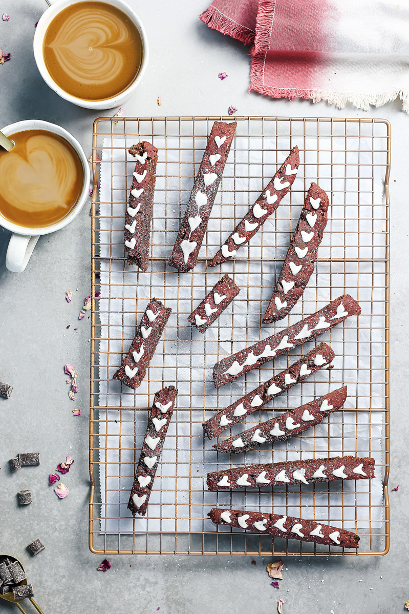 Red Velvet Biscotti by Pasta-based. A wide overhead shot of the biscotti laying on a cooling rack with white icing hearts. Two coffees are on the table waiting to be dipped into.