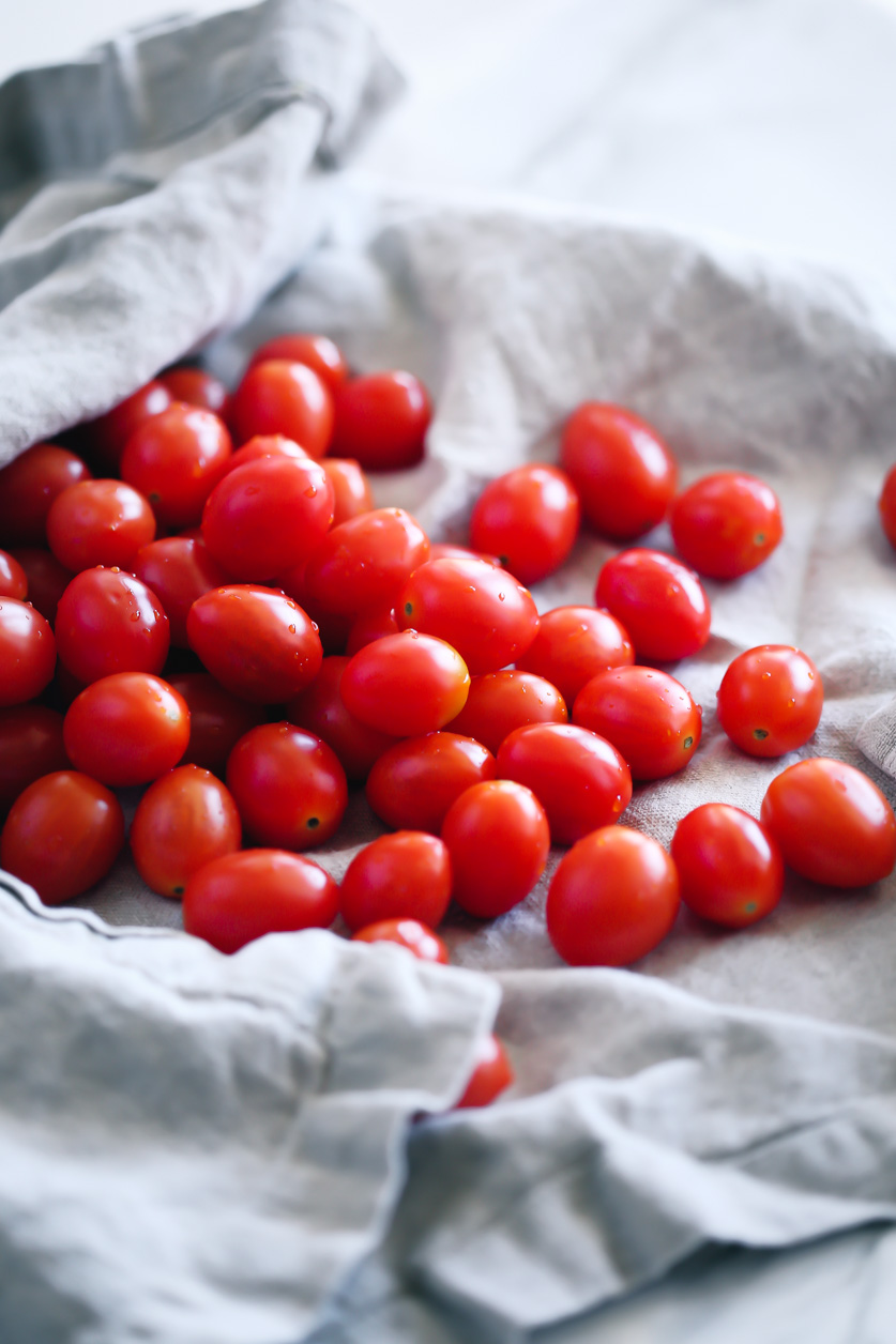 easy, simple, fresh grape tomato sauce by pasta-based. beautiful, bright red, plump grape tomatoes with droplets of water spilling out of a soft linen towel.