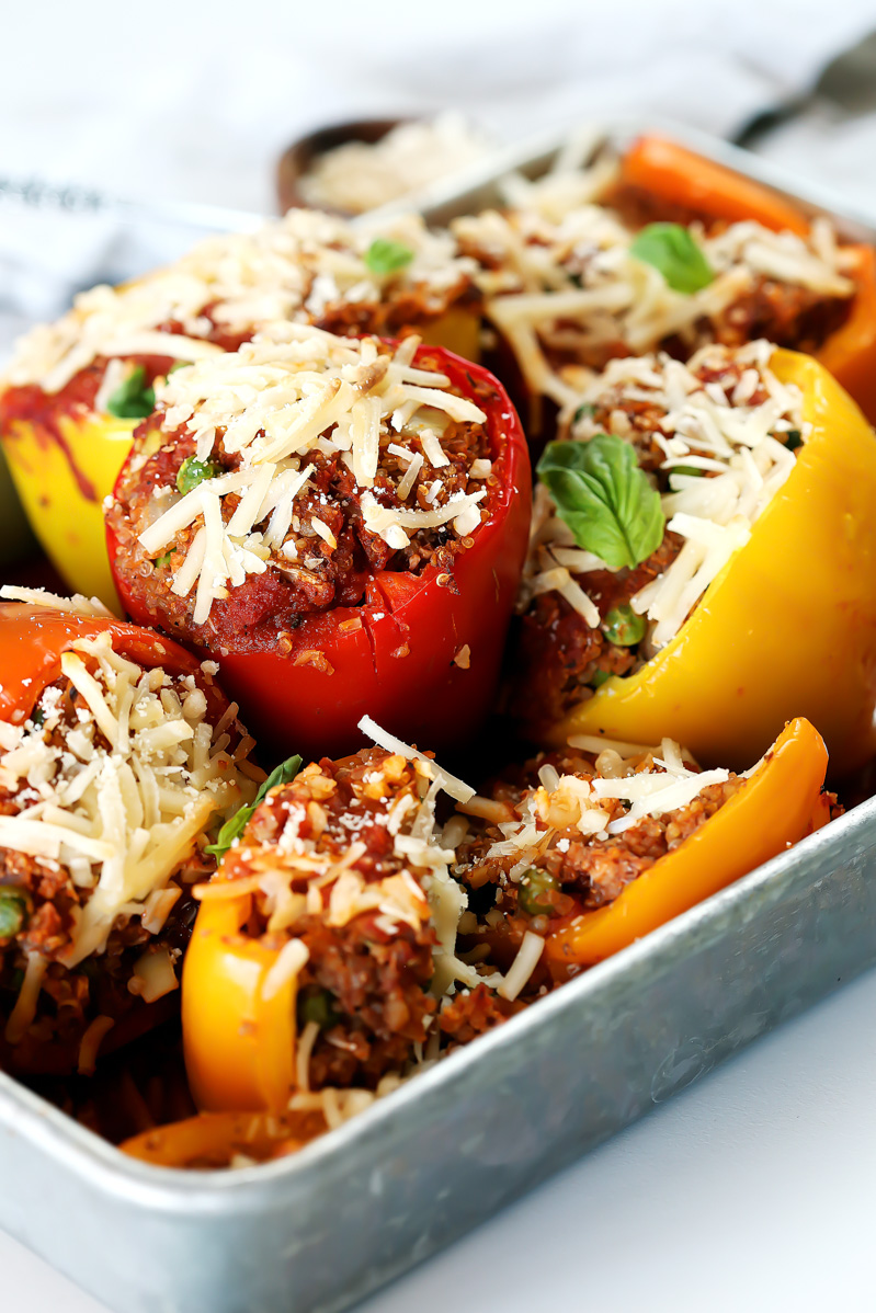 vegan stuffed peppers by pasta-based. six stuffed peppers together in a silver pan.