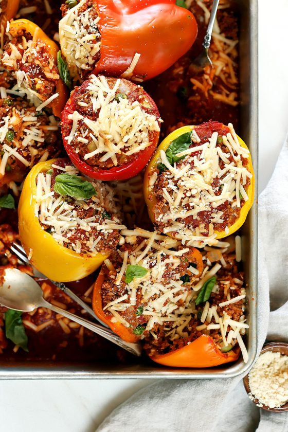 vegan stuffed peppers by pasta-based. vegan quinoa stuffed bell peppers in red, orange, and yellow gathered in a large silver pan with vegan mozzarella cheese and extra marinara sauce on top.