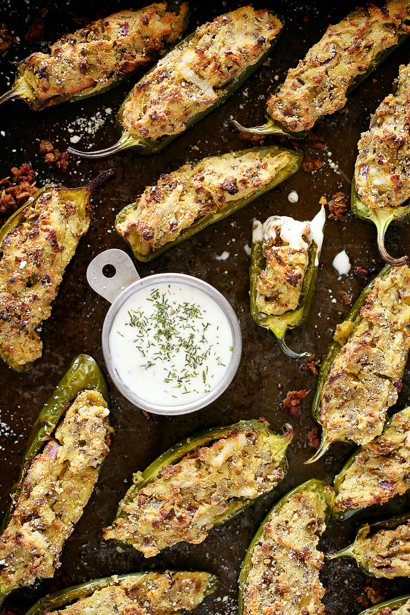 Vegan Jalapeno Poppers by Pasta-based. Beautiful, bursting, crispy, jalapeno poppers stuffed with vegan ricotta and sausage crumbles sprawled out on a dark grey baking sheet. Small bowl of vegan ranch with fresh dill and a jalapeno drenched in ranch with a bite taken out.