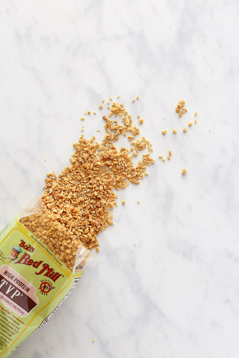 Vegan Italian Sausage Crumbles by Pasta-based. Textured Vegetable Protein (TVP) from Bob's Red Mill spills out of the bag onto a clean marble countertop. The TVP is a yellowy-brown and looks crunchy in texture.