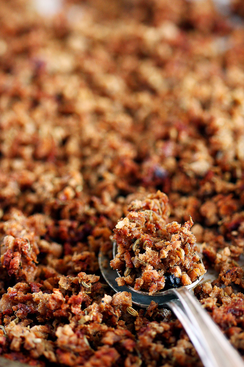 Vegan Italian Sausage Crumbles by Pasta-based. The camera zooms into the vegan Italian sausage crumbles which look mouthwatering straight out of the oven. They are darker in color, crispy in texture, and loaded with aromatic spices like dried fennel seeds which you can see in the photo. Two spoons overlapping lay on the pan with a pile of vegan Italian sausage crumbles in the top spoon.