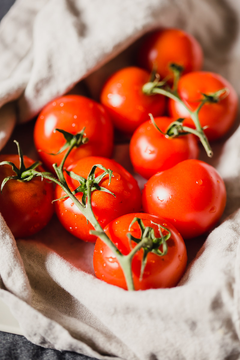 Oven Roasted Campari Tomatoes by Pasta-based. Beautiful bright red campari tomatoes on the vine, washed and wrapped in a linen towel.