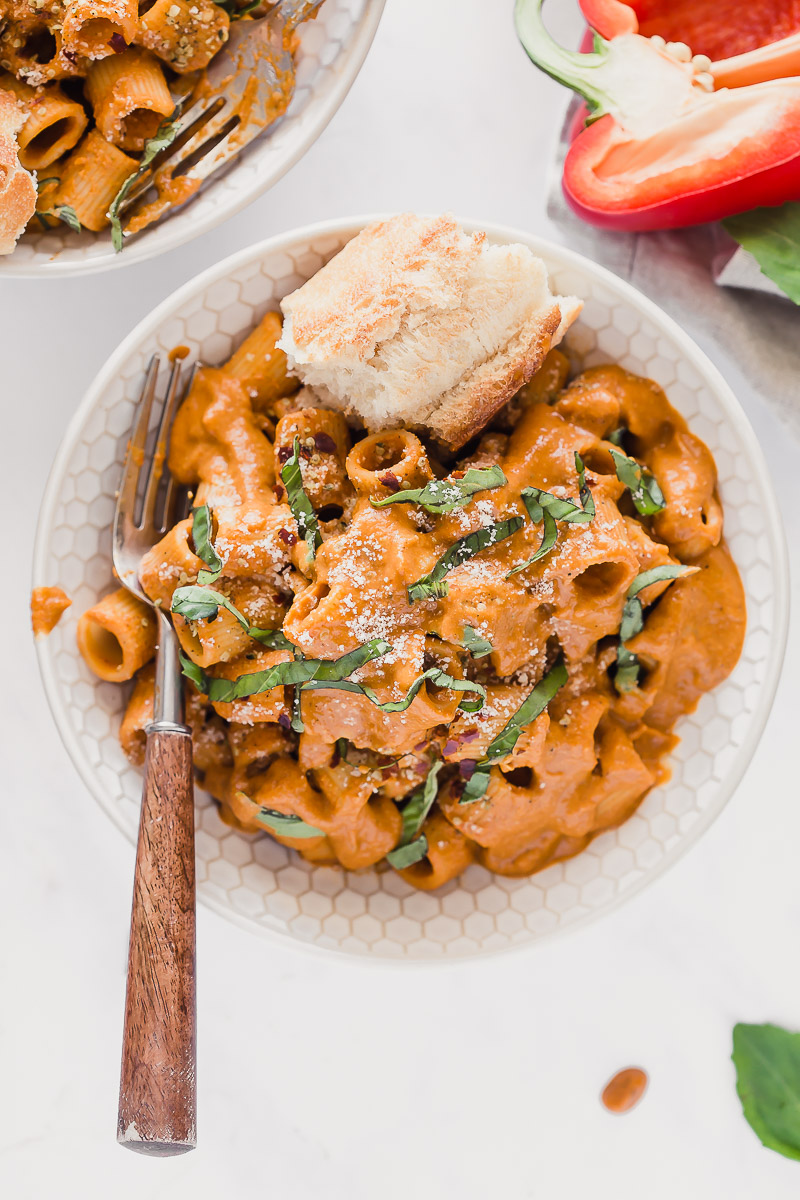 Vegan Roasted Red Pepper Pasta Sauce by Pasta-based. An overhead photo of a bowl of rigatoni smothered with creamy roasted red pepper sauce and a piece of crusty Italian bread on the side. Ribbons of basil leaves sprinkled on top and a fork with a wooden handle rested on top. This pasta is ready to be devoured!