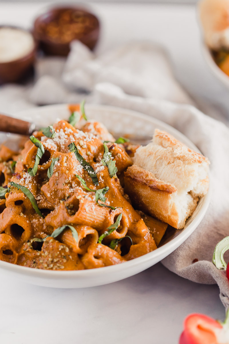 Vegan Roasted Red Pepper Pasta Sauce by Pasta-based. A bowl of rigatoni smothered with creamy roasted red pepper sauce and a piece of crusty Italian bread on the side.