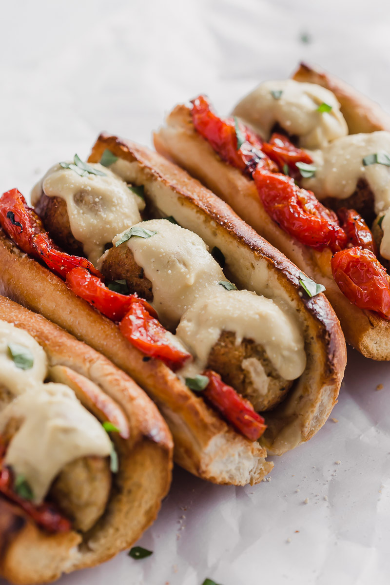 Vegan Meatball Subs by Pasta-based. Four meatball heroes on toasted garlic bread with roasted campari tomatoes, vegan cauliflower alfredo sauce, and cauliflower brown rice meatballs with fresh basil sprinkled around.