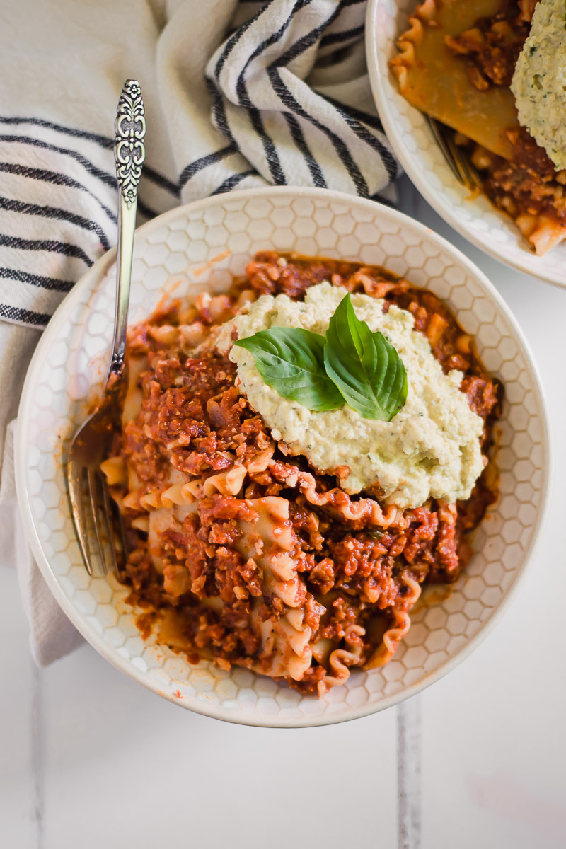Vegan Lasagna Bowl by Pasta-based. All the ingredients of a lasagna but in a bowl! A large bowl stuffed with lasagna noodles, vegan ricotta cheese with two fresh basil leaves on top, and a vegan meat sauce made with cauliflower and walnuts.