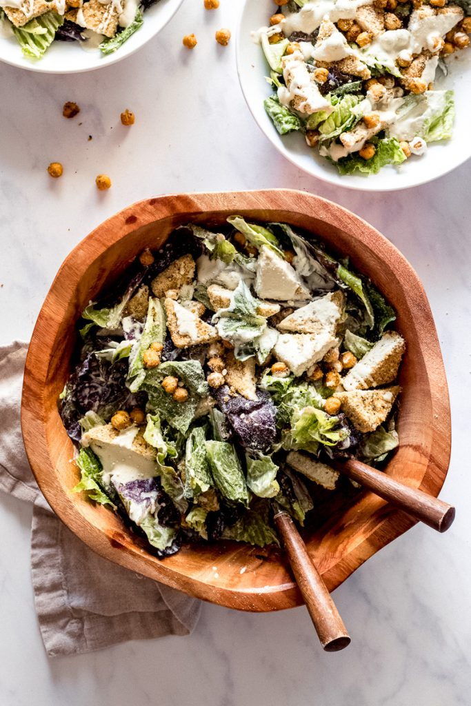 Brown wood bowl with lettuce, crispy tofu, crispy chickpeas and vegan caesar dressing drizzled on top.