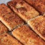 Crispy breaded and pan-fried vegan tofu cutlets lined up in a row. The breadcrumb coating looks golden brown and delicious.
