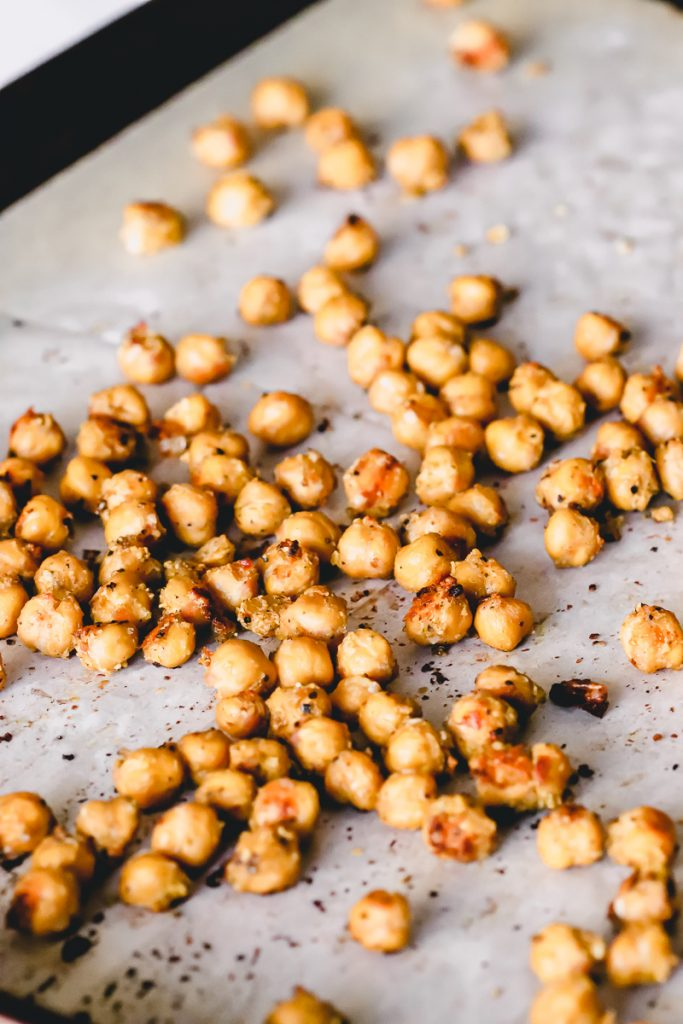 A baking sheet with crispy chickpeas scattered.