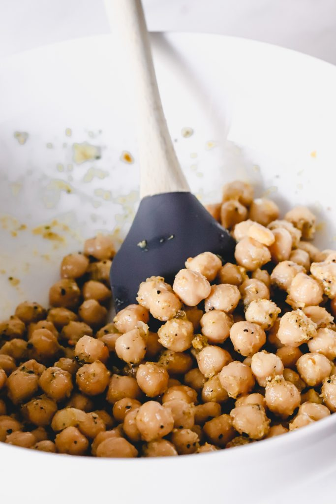 A mixing bowl of chickpeas with oil/herbs coating them and a silicone spatula.
